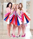 Gelukkige jonge groep vrouwen na het winkelen in de grote wandelgalerij stock afbeeldingen