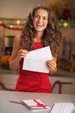 Gelukkige jonge huisvrouw die Kerstmisbrief zetten in envelop Stock Afbeeldingen