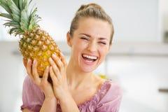 Gelukkige jonge huisvrouw die verse ananas houden Stock Foto's