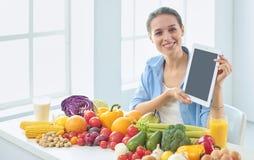 Gelukkige jonge huisvrouwenzitting in de keuken die voedsel van een stapel van diverse verse organische vruchten en groenten voor stock foto's