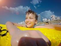 Gelukkige jonge jongen in de oceaan op surfplank stock foto