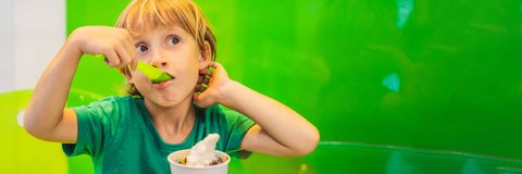Gelukkige jonge jongen die een smakelijk roomijs of een bevroren yoghurtbanner, LANG FORMAAT eten stock afbeeldingen