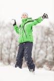 Gelukkige jonge jongen die een sneeuwbalstrijd hebben Stock Afbeeldingen