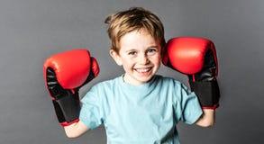 Gelukkige jonge jongen die met sproeten grote bokshandschoenen houden Stock Afbeeldingen