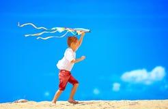 Gelukkige jonge jongen die met vlieger op hemelachtergrond lopen Royalty-vrije Stock Afbeeldingen