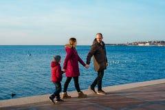 Gelukkige jonge Kaukasische familie met oude zoon lopen het van vijf jaar langs steenachtige pier op zonneschijn, achtermening Ge stock afbeelding
