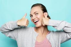 Gelukkige jonge Kaukasische vrouwelijke het maken duim omhoog om te ondertekenen en cheerfully het glimlachen stock fotografie