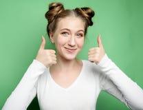 Gelukkige jonge Kaukasische vrouwelijke het maken duim omhoog om te ondertekenen en cheerfully het glimlachen stock foto's