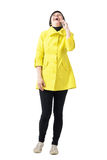 Gelukkige jonge korte haarvrouw die in gele laag luid op de mobiele telefoon lachen Stock Foto's