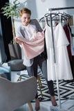 gelukkige jonge manierontwerper die kwaliteit van kleding onderzoeken royalty-vrije stock fotografie