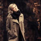 Gelukkige jonge maniervrouw die in beige laag in de herfstpark lopen royalty-vrije stock fotografie