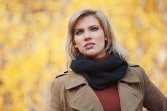 Gelukkige jonge maniervrouw die in beige laag in de herfstpark lopen royalty-vrije stock foto's