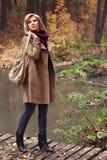 Gelukkige jonge maniervrouw die met handtas in de herfstpark lopen stock afbeelding