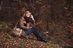 Gelukkige jonge maniervrouw met handtaszitting op grond in de herfstpark stock foto