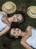 Gelukkige jonge meisjes die bij groen gras en het dromen liggen mening van hierboven, zacht Stock Foto