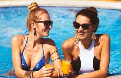 Gelukkige jonge meisjes met dranken op de zomerpartij dichtbij de pool stock foto's