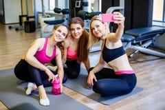Gelukkige jonge meisjes in sportkleding die selfie in gymnastiek nemen Drie vrouwelijke vrienden in healthclub die selfie met mob royalty-vrije stock foto's