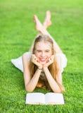 Gelukkige jonge meisjeslezing op het gras stock fotografie