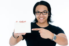 Gelukkige jonge mens die aan leeg adreskaartje richt Stock Foto's