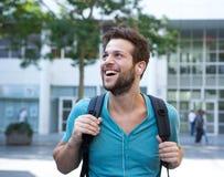 Gelukkige jonge mens die aan muziek op oortelefoons luisteren Stock Afbeelding