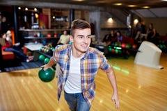 Gelukkige jonge mens die bal in kegelenclub werpen Stock Foto's