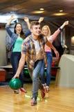 Gelukkige jonge mens die bal in kegelenclub werpen Royalty-vrije Stock Afbeeldingen