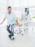Gelukkige jonge mens die in bureau met een skateboard rijden Royalty-vrije Stock Fotografie