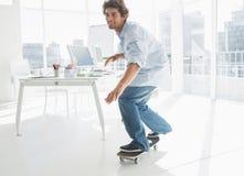 Gelukkige jonge mens die in bureau met een skateboard rijden Stock Afbeeldingen