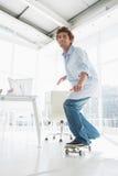Gelukkige jonge mens die in bureau met een skateboard rijden Royalty-vrije Stock Foto's