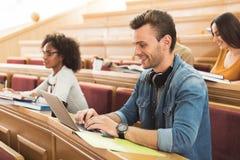 Gelukkige jonge mens die computer met behulp van tijdens lezing royalty-vrije stock foto
