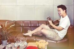 Gelukkige jonge mens die de gitaar in woonkamer spelen stock afbeeldingen