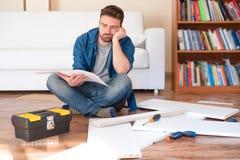 Gelukkige jonge mens die de instructies lezen om meubilair te assembleren stock foto's