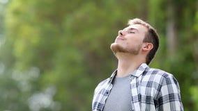 Gelukkige jonge mens die diep in openlucht ademen stock footage