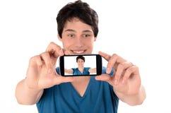 Gelukkige jonge mens die een selfiefoto met zijn slimme telefoon nemen Stock Afbeeldingen