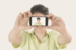 Gelukkige jonge mens die een selfiefoto met zijn slimme telefoon nemen Stock Foto