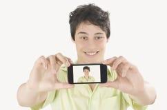 Gelukkige jonge mens die een selfiefoto met zijn slimme telefoon nemen Mens Royalty-vrije Stock Afbeelding