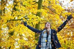 Gelukkige jonge mens die en bladeren met open wapens glimlachen werpen Royalty-vrije Stock Afbeeldingen
