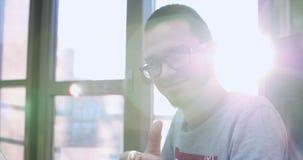 Gelukkige jonge mens die glazen dragen die bij lijst zitten, het werk aangaande computer doen, en camera op achtergrond draaien b stock footage