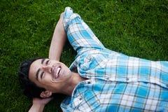 Gelukkige jonge mens die in gras ligt Royalty-vrije Stock Foto