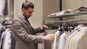 Gelukkige jonge mens die kleren in kledingsopslag kiezen stock footage