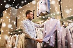 Gelukkige jonge mens die kleren in kledingsopslag kiezen Royalty-vrije Stock Fotografie