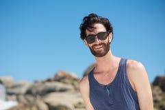 Gelukkige jonge mens die met zonnebril glimlachen Stock Afbeeldingen