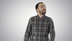 Gelukkige jonge mens die omhoog terwijl het lopen op gradi?ntachtergrond kijken stock video