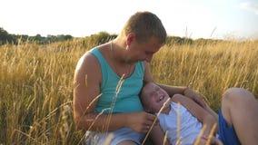 Gelukkige jonge mens die op gras bij het gebied liggen en met zijn babyjongen spelen Vrolijke papa en zijn kind die pret hebben stock footage