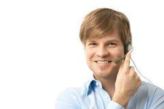 Gelukkige jonge mens die op hoofdtelefoon spreekt Stock Foto