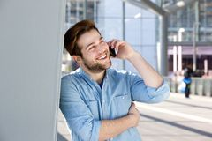 Gelukkige jonge mens die op mobiele telefoon spreekt Royalty-vrije Stock Foto's