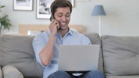 Gelukkige Jonge Mens die op Telefoon spreken en aan Laptop werken stock video