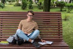 Gelukkige jonge mens die in openlucht bestuderen stock afbeeldingen