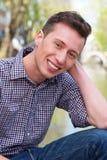 Gelukkige jonge mens die in openlucht ontspannen Stock Foto