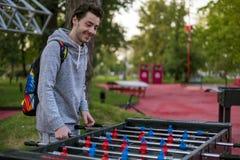 Gelukkige jonge mens die tablefootball in een park in Moskou spelen stock afbeelding